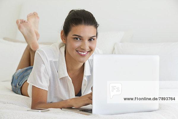 Frau mit einem Laptop auf dem Bett