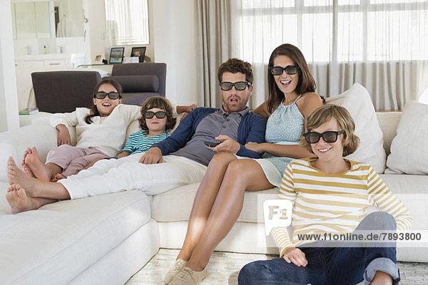 Familie beim Fernsehen zu Hause mit 3D-Brille