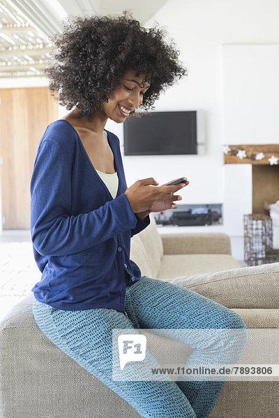 Lächelnde Frau SMS auf dem Handy