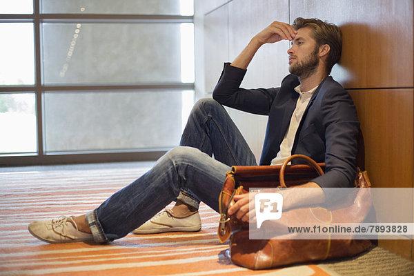 Mann lehnt sich an die Wand eines Flughafens