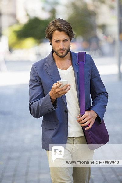 Man walking on a street using a mobile phone