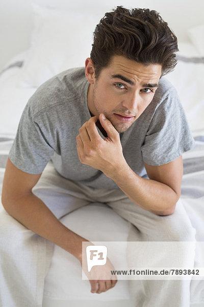 Mann auf dem Bett sitzend