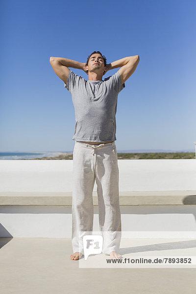 Mann stehend mit Händen hinter dem Kopf