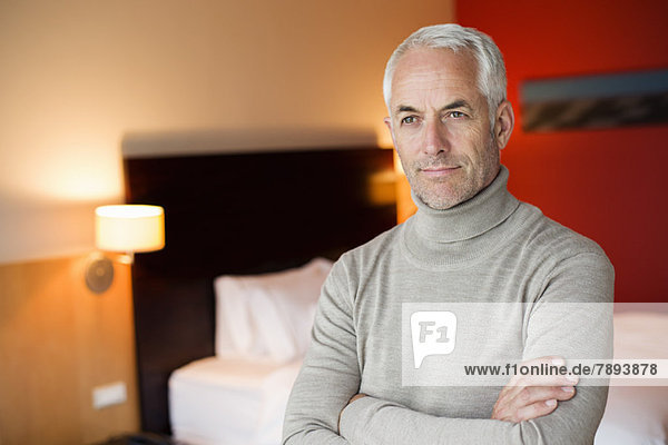Man with arms crossed in a hotel room