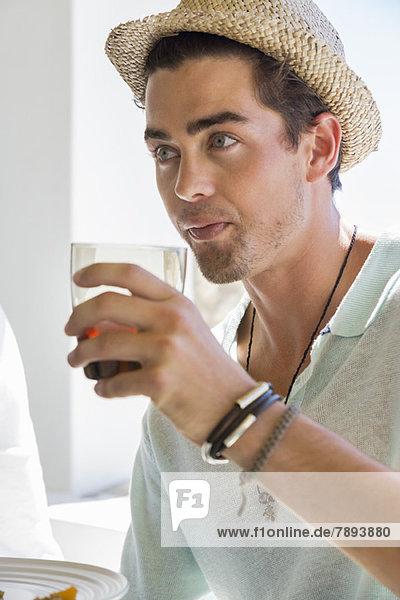 Mann trinkt Rotwein am Esstisch