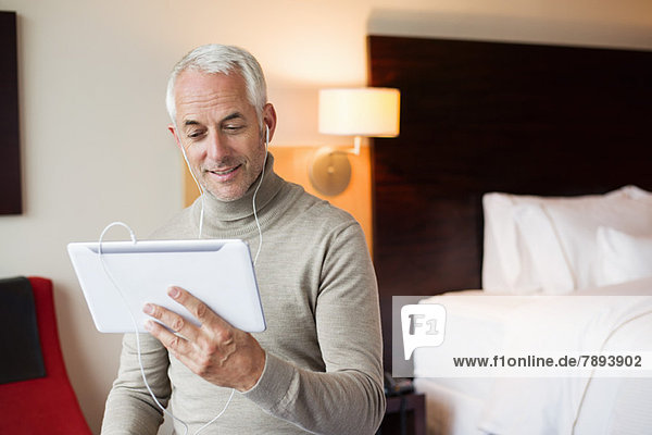 Man watching a movie on digital tablet in a hotel room