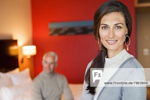 Porträt einer lächelnden Frau im Hotelzimmer mit ihrem Mann im Hintergrund