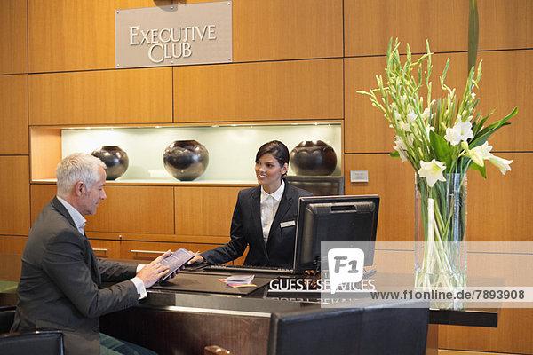 Geschäftsmann beim Lesen einer Broschüre an der Hotelrezeption