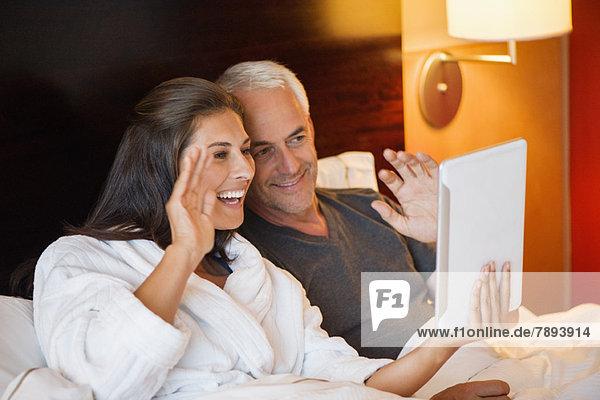 Paar Videoanrufe auf einem digitalen Tablett in einem Hotelzimmer