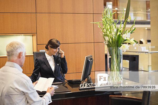 Geschäftsmann beim Lesen einer Broschüre mit einer Empfangsdame  die am Telefon an der Hotelrezeption spricht.