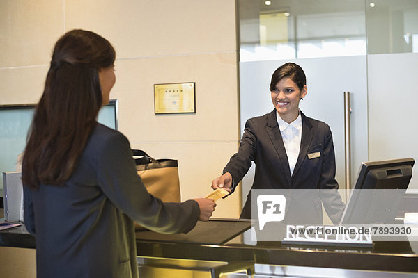 Geschäftsfrau beim Bezahlen mit Kreditkarte an der Hotelrezeption