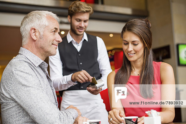 Paar  das mit einer Kreditkarte an einen Kellner in einem Restaurant zahlt.