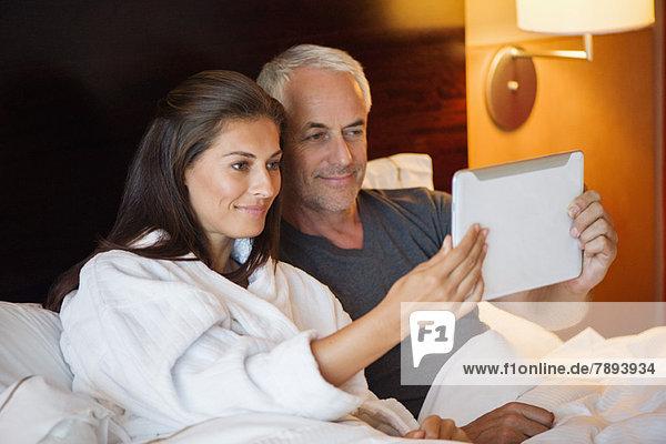 Ein Paar schaut sich einen Film auf einem digitalen Tablett in einem Hotelzimmer an.