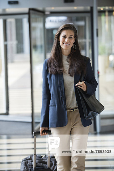 Geschäftsfrau beim Kofferziehen in der Hotellobby