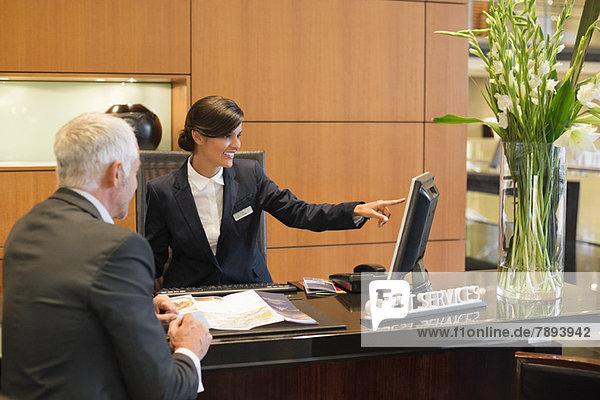 Rezeptionist  der mit einem Geschäftsmann auf einen Desktop-PC an der Hotelrezeption zeigt.