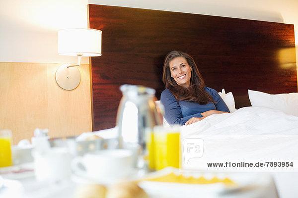 Frühstück auf dem Tisch vor einer Frau im Hotelzimmer