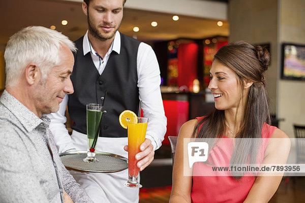 Kellner  der einem Paar in einem Restaurant Getränke serviert.