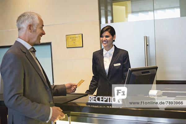 Geschäftsmann beim Bezahlen mit Kreditkarte an der Hotelrezeption