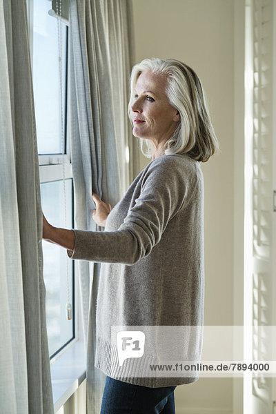 Frau am Fenster stehend