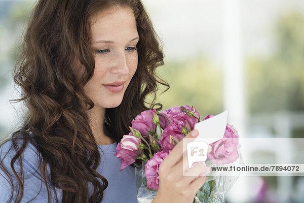 Frau beim Lesen einer Karte mit Blumenstrauß