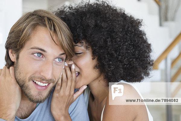 Frau flüstert einem Mann zu.