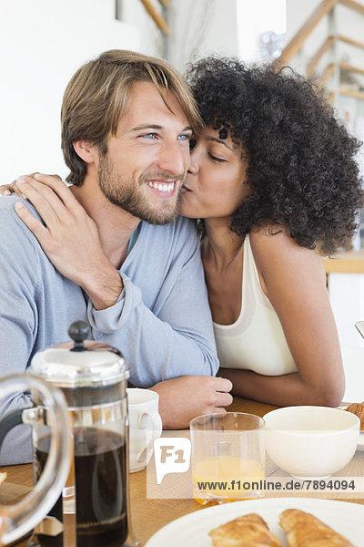 Frau beim Küssen ihres Mannes am Esstisch
