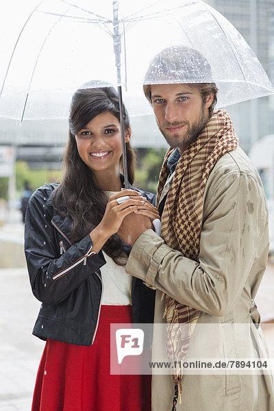 Porträt eines lächelnden Paares unter einem Regenschirm