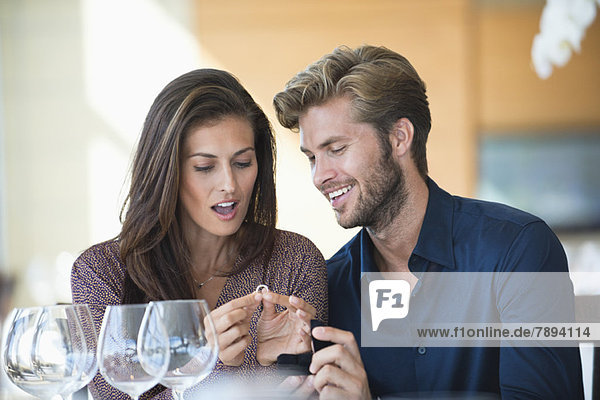 Man giving engagement ring to his girlfriend in a restaurant
