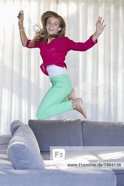 Porträt eines lächelnden Mädchens  das auf einer Couch springt.
