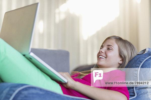Mädchen  das auf einer Bohnentüte liegt und einen Laptop benutzt