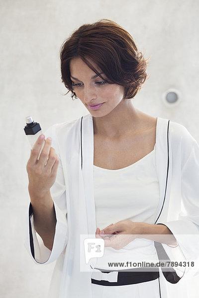 Frau betrachtet ein Kosmetikprodukt