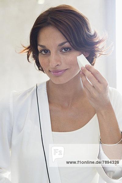 Frau  die Kosmetik auf ihr Gesicht aufträgt.