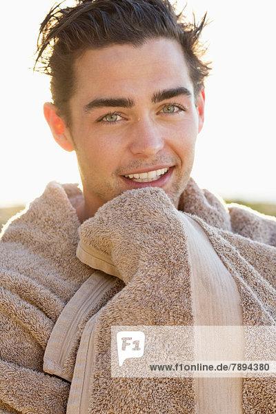 Porträt eines lächelnden Mannes in ein Handtuch gewickelt