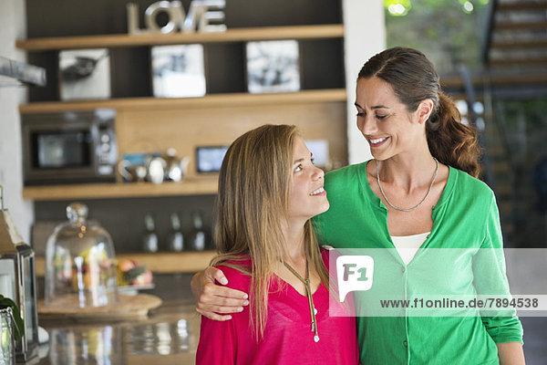 Frau lächelt mit ihrer Tochter zu Hause