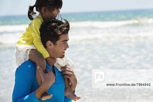 Mann  der seine Tochter auf den Schultern am Strand trägt.