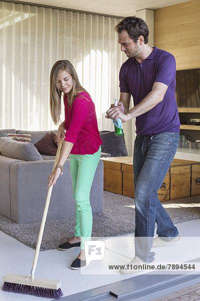 Mädchen beim Putzen mit einem Wischmopp neben ihrem Vater
