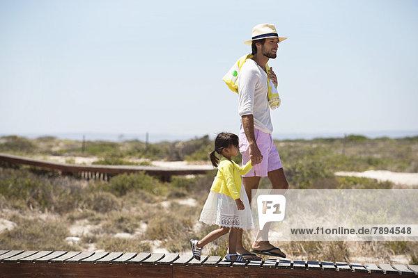 Mann mit seiner Tochter auf einer Promenade am Strand