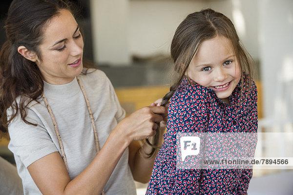 Lächelnde Frau  die das Haar ihrer Tochter flechtet.