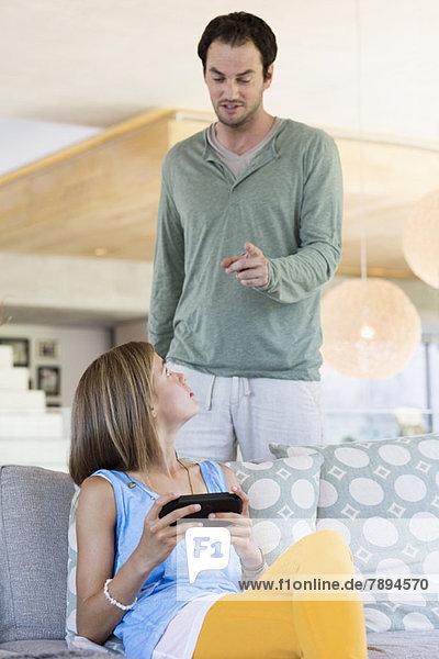 Mann schimpft mit seiner Tochter wegen des Videospiels.