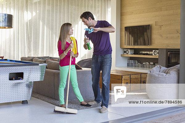 Vater und Tochter halten Reinigungsgeräte in der Hand und diskutieren über