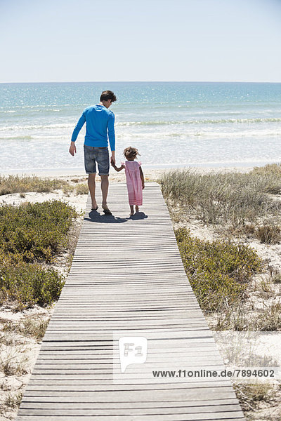 Man with his daughter walking on a boardwalk on the beach