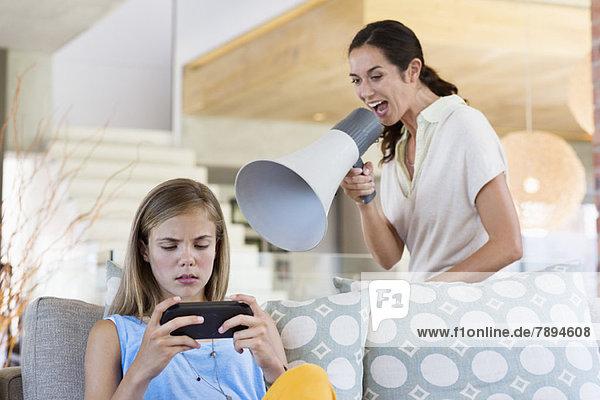 Frau schreit durch ein Megaphon seine Tochter an  weil sie Videospiel spielt.