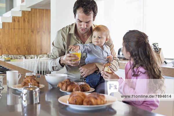 Familie beim Frühstück an der Küchenzeile