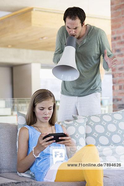 Ein Mann  der seine Tochter wegen eines Videospiels anschreit.