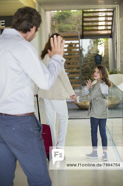 Ein Mann winkt seiner Tochter zu  die das Haus verlässt.