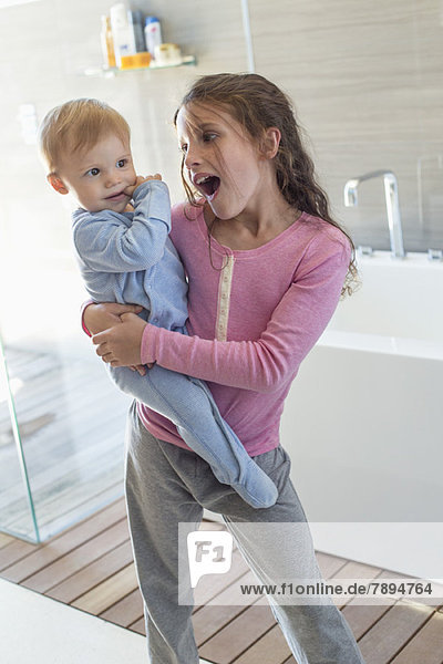 Mädchen trägt ihren Bruder und sieht überrascht in einem Badezimmer aus.