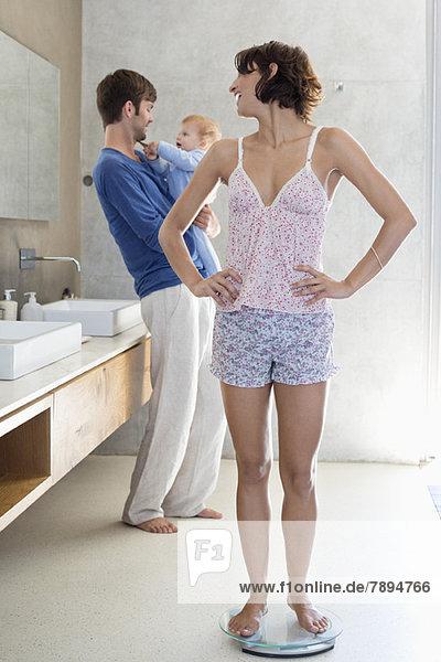 Frau misst ihr Gewicht auf einer Waage mit ihrem Mann und Sohn im Badezimmer.