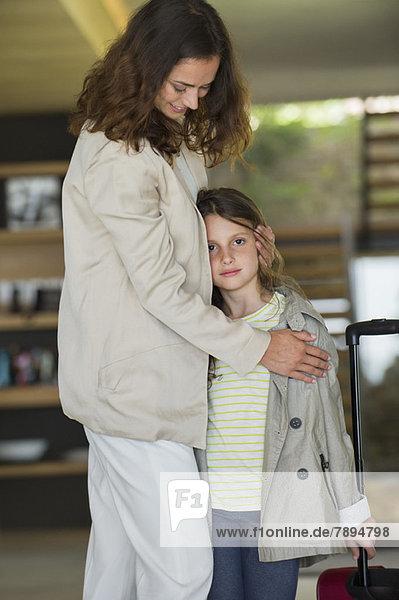 Lächelnde Frau umarmt ihre Tochter