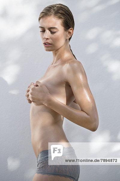 Frau versteckt ihre Brust mit ihren Händen