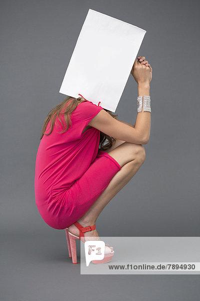 Frau hält eine Einkaufstasche über ihr Gesicht